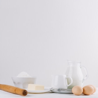 Cheese; flour; milk; rolling pin; whisker and eggs on white backdrop for making pie