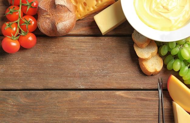 나무 테이블에 치즈 퐁듀와 다양한 제품