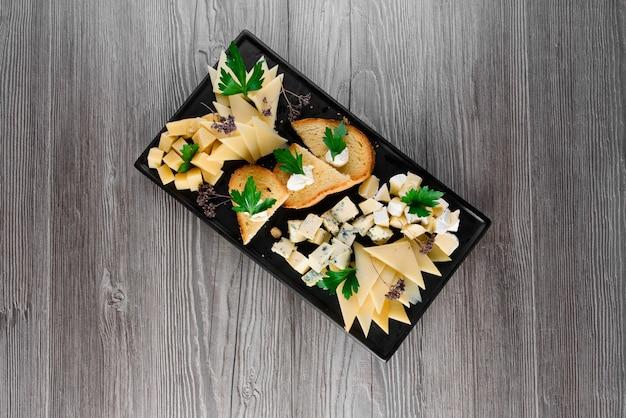 Доска сырная с нежными сырами, грецкими орехами. пармезан, джем, дорблю на черной тарелке. еда закуска из ресторана.