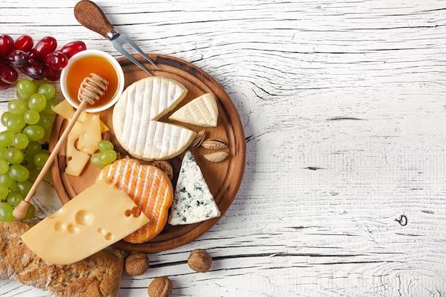 커팅 보드와 흰색 나무 테이블에 치즈, 포도, 꿀, 견과류. 평면도.