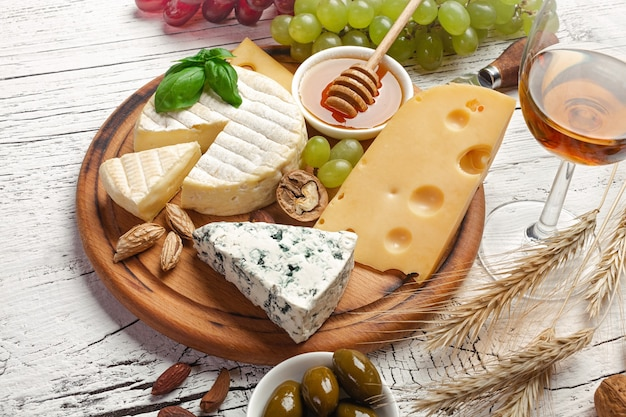 Cheese, grape, honey and nuts on cutting board and white wooden table. top view.