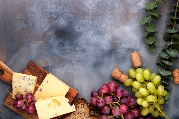 Cheese and grapes on a black gray concrete background