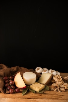 Cheese, grapes, garlic and healthy snack against black backdrop