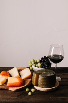Cheese and grapes near wine
