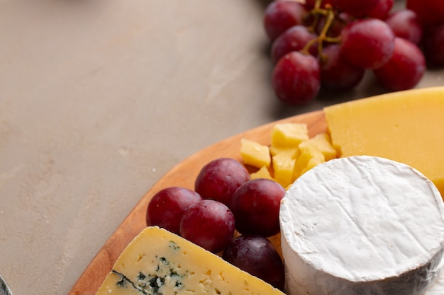 Cheese and grapes on plate close up