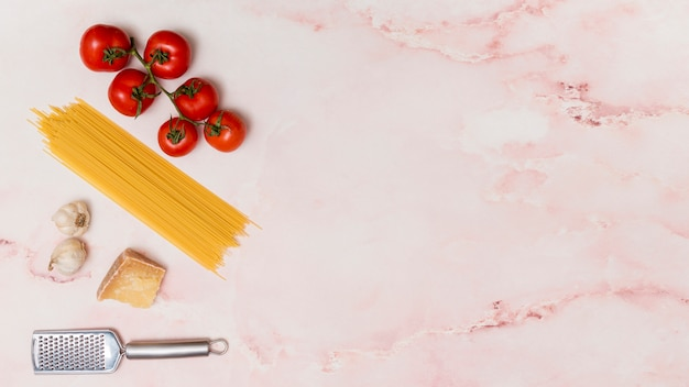 Cheese; grater; garlic; uncooked spaghetti pasta and red fresh tomatoes with copy space over pink marble textured background