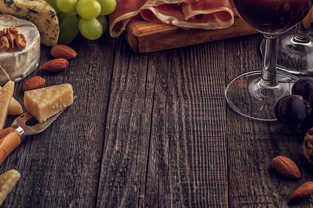 チーズ、ハム、ナッツ、ブドウ、木製の表面に赤ワイン