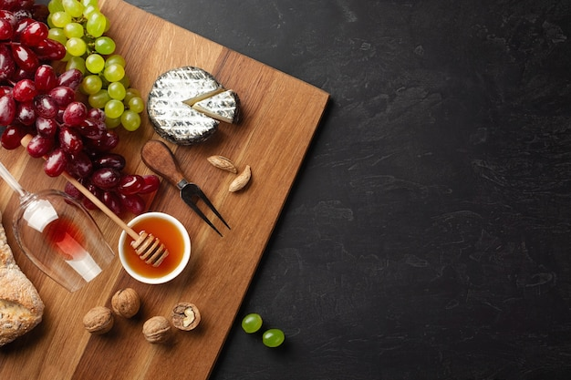 Cheese head, bunch of grapes, honey, nuts and wineglass on wooden board and black background. top view with copy space.