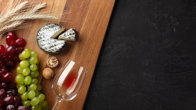 Cheese head, bunch of grapes, nuts and wineglass on wooden board and black background. top view with copy space.