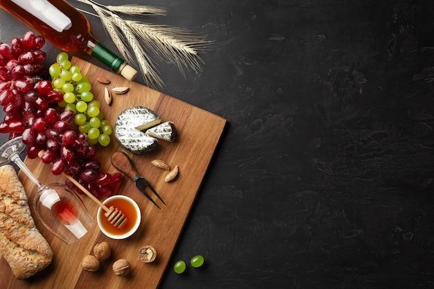 치즈 머리, 포도, 꿀, 견과류, 와인잔이 나무 판자에 있고 검은색 배경에 있습니다. 복사 공간이 있는 상위 뷰입니다.