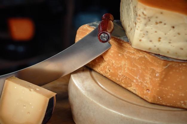 Сырные головки с кусочками и ножами на деревянной доске с интерьером