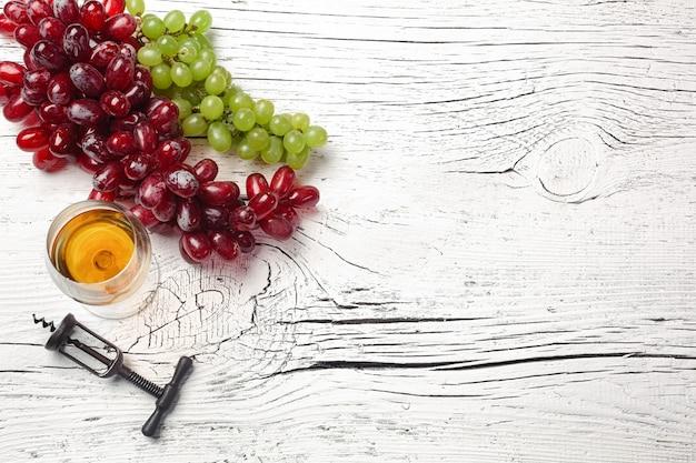 白い木の板にチーズ、蜂蜜、ブドウ、ナッツ、ワイングラス。コピースペースのある上面図。