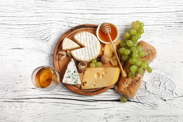 Cheese, honey, grape, nuts and wineglass on cutting board and white wooden table. top view.