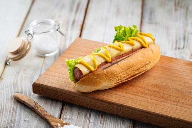 木の板にマスタードとチーズのホットドッグ