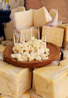 Сыр на рынке и тарелка, чтобы попробовать продукт бесплатно