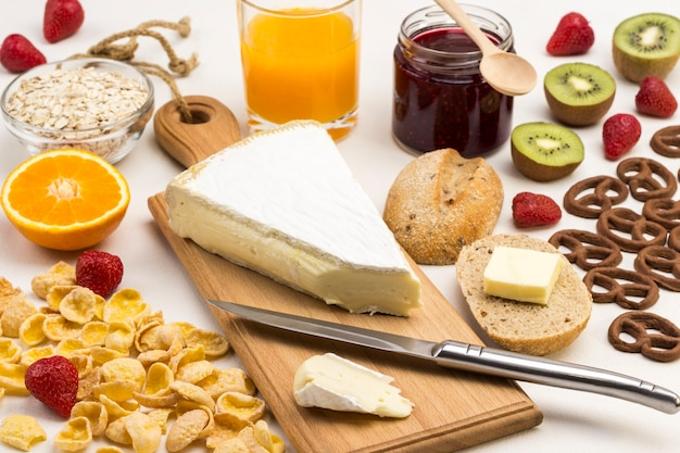 Cheese and knife on cutting board. cereal, cookies juice, fruit jam. white surface. ingredients for english breakfast. balanced diet. top view