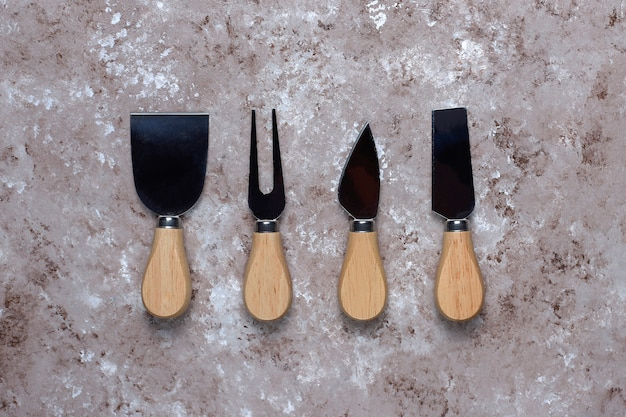 Cheese knives with wooden handles, fork, spatula on light brown surface.