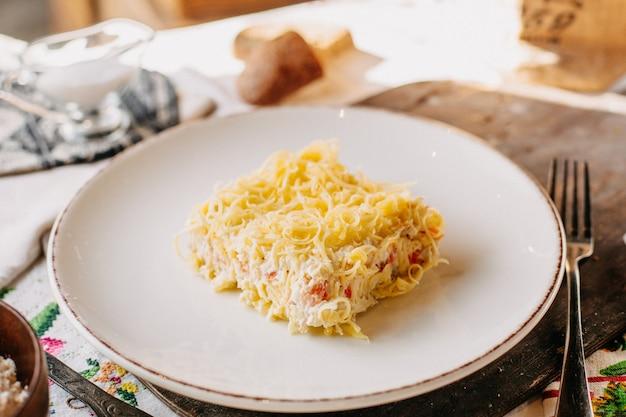 Insalata di maionese al formaggio salato pepato gustoso all'interno del piatto bianco sulla scrivania in legno marrone