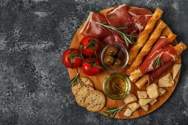 Cheese and meat appetizer selection with prosciutto, parmesan, bread sticks