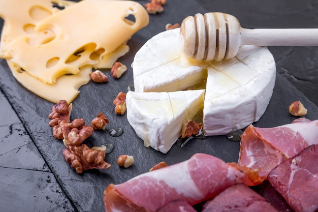 Cheese and meat plate with walnuts on black slate plate