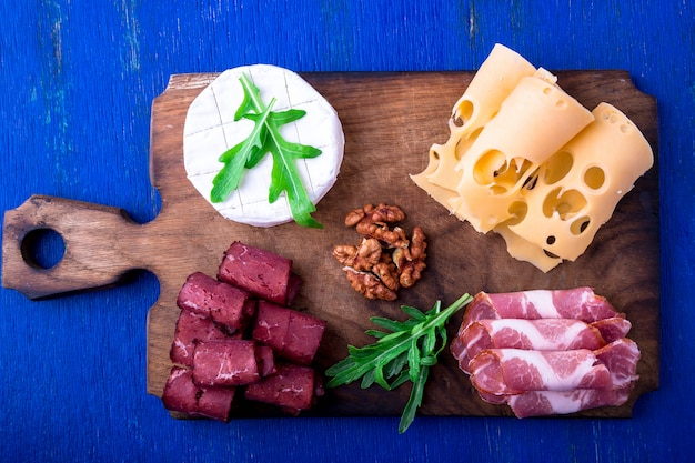 Cheese and meat plate with walnuts on blue wooden surface,