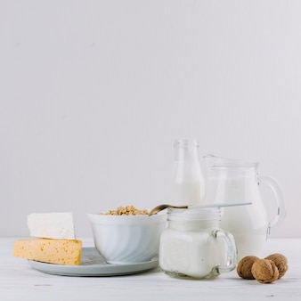 Cheese; milk; bowl of cereals and walnuts over white backdrop