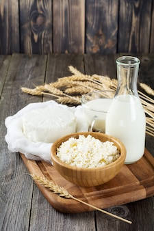 Cheese, milk, cottage cheese and wheat on old wooden