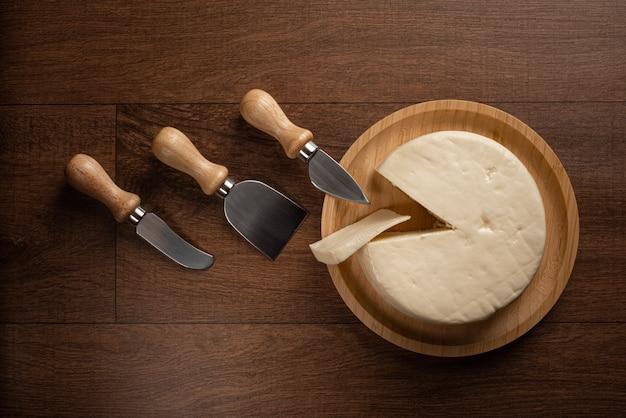 チーズ、木の表面にチーズアクセサリーが付いた木製プレート上のブラジル産ミナスチーズ、上面図。