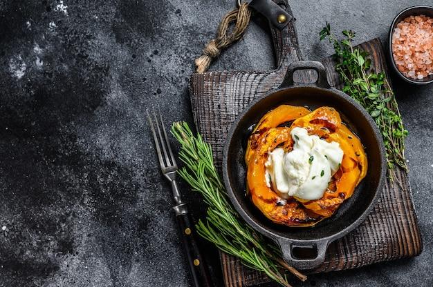 치즈 모짜렐라 burrata와 구운 호박 샐러드. 검정색 배경. 평면도. 공간을 복사하십시오.