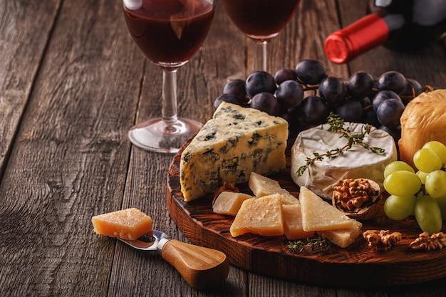 チーズ、ナッツ、ブドウ、木製の表面に赤ワイン