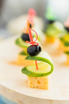 Cheese, olive and cucumber on plastic skewer on plate