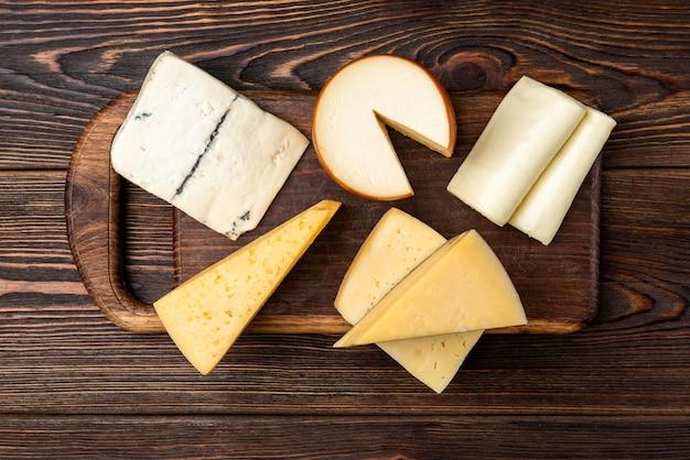 Сыр на темном деревянном фоне.