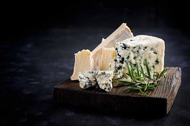 Сыр на деревянных досках. камамбер и дорблю на деревянных фоне. молочные продукты Premium Фотографии