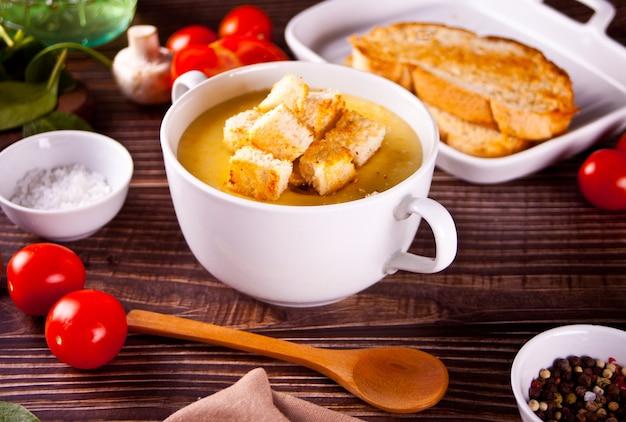 Сырный или луковый крем-суп с гренками в белой миске