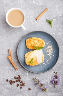 Cheese pancakes on a blue ceramic plate and a cup of coffee on gray concrete
