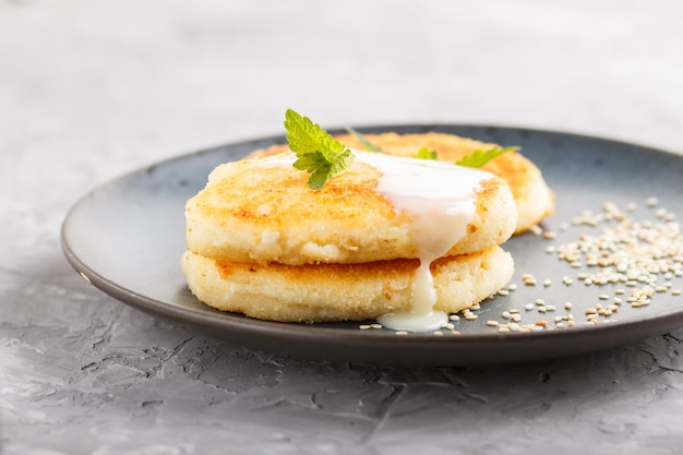 Cheese pancakes on a blue ceramic plate with milk sauce on gray concrete