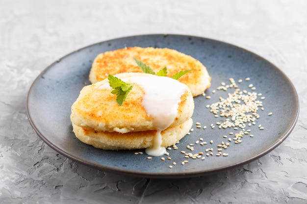 Cheese pancakes on a blue ceramic plate with milk sauce on a gray concrete.