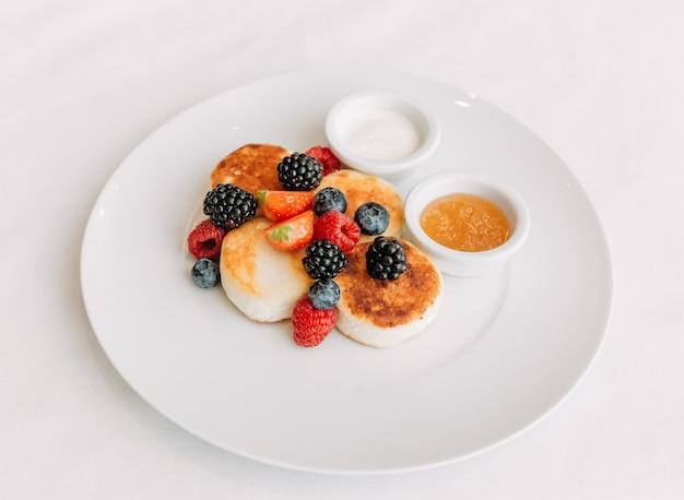 Сырные блины со свежими ягодами в белой тарелке и сметаной и медом, вид сверху