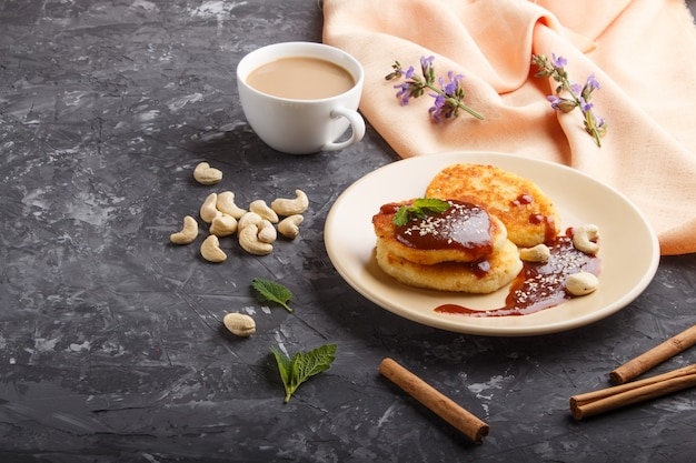 Cheese pancakes with caramel sauce on a beige ceramic plate and a cup of coffee on black concrete