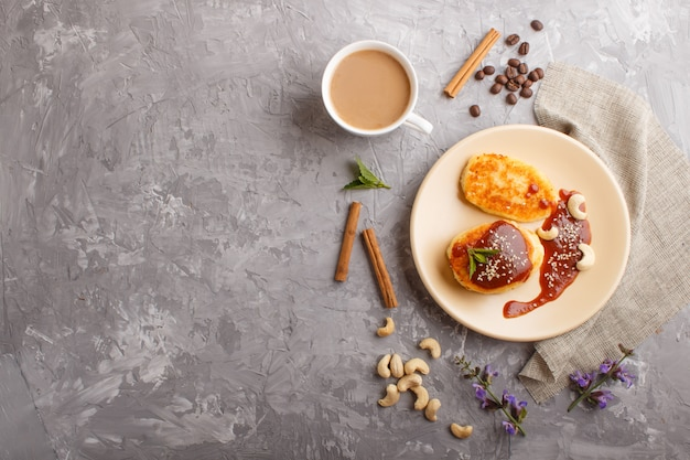 Cheese pancakes with caramel sauce on a beige ceramic plate and a cup of coffee on gray concrete