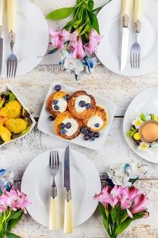 Сырные оладьи со сметаной и свежей черникой на праздничном столе.