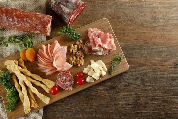Сыр, пармская ветчина, салями, филе, колбаса с оливками и специями на деревянной доске