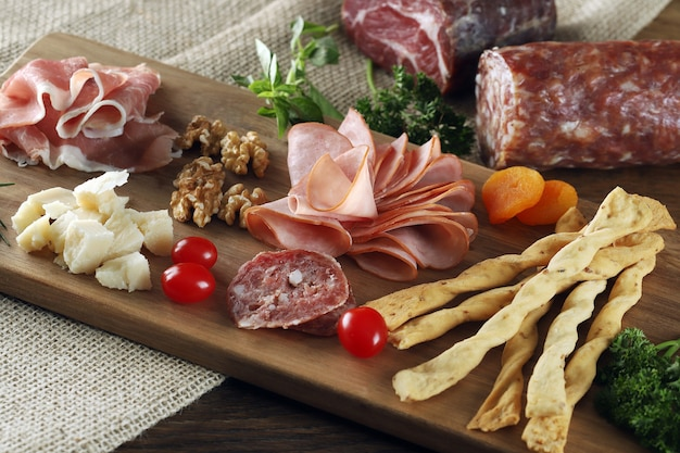 Cheese, parma ham, salami, sirloin, sausage with olives and spices on wooden board.