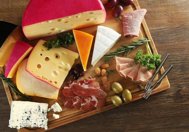 Сыр, пармская ветчина, филе и колбаса с оливками на деревянной доске