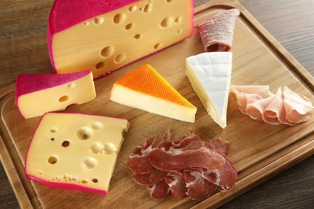 Сыр, пармская ветчина, филе и колбаса с оливками на деревянной доске.