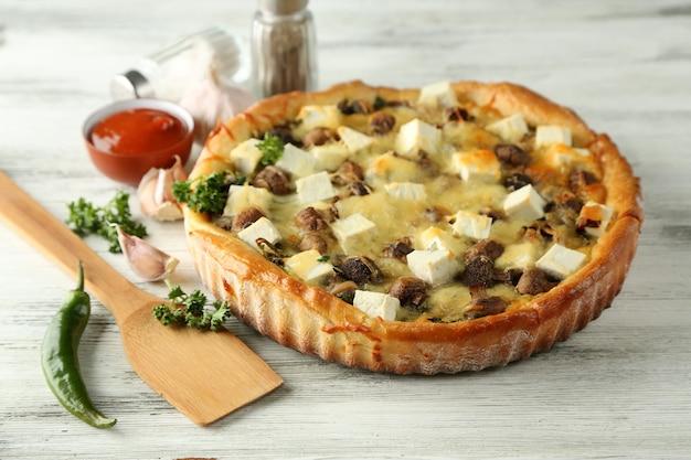 木製のテーブルの表面に、きのこ、ハーブ、サワークリームのチーズパイ
