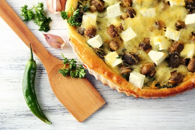 Сырный пирог с грибами, зеленью и кислым кремом на деревянном столе
