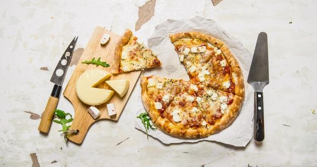 Сырная пицца с зеленью и свежим сыром. на деревенском фоне. вид сверху