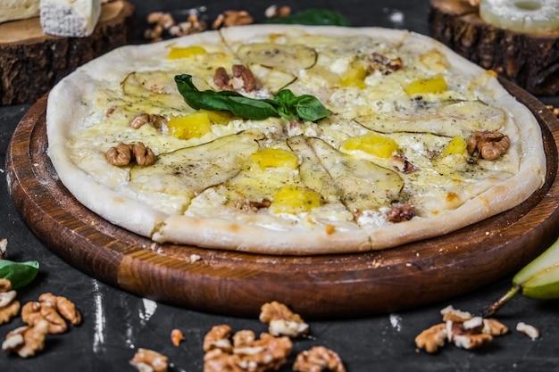어두운 표면에 배와 견과류와 치즈 피자