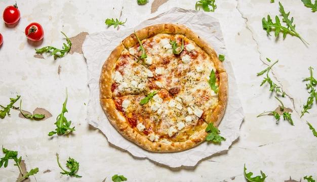 Сырная пицца с помидорами и зеленью. на деревенском фоне. вид сверху